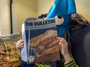 The picture shows a young reader wearing a funny hat and reading a recent issue of the Bulletin.
