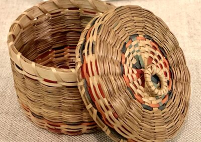 A small, woven basket with a lid from the Robbins Museum.